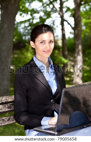 young pretty woman with laptop on the bench in a park - stock photo