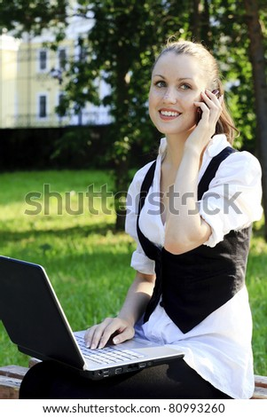 Young pretty woman with laptop sitting on the bench in a park.
