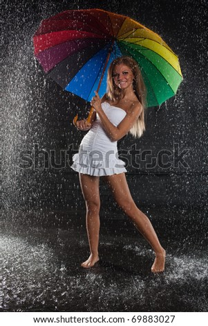 Young pretty woman with multi-coloured umbrella under rain on a black background. - stock photo
