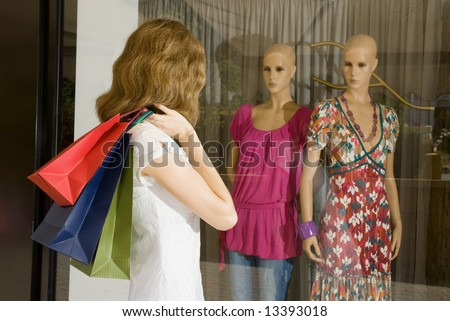 Young pretty woman with paper bags looking at mannequins in shop window - stock photo