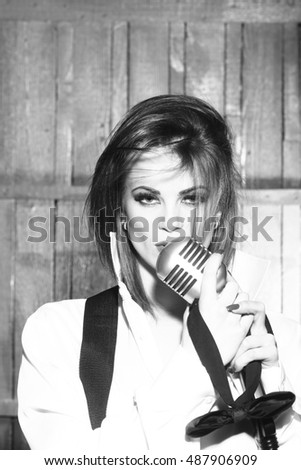 young pretty woman with sexy lips singing into silver studio microphone in retro braces and shirt holding bow, closeup, black and white