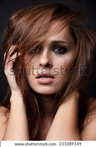Young pretty woman with smeared mascara crying on black background - stock photo