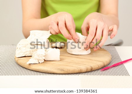 Young pretty woman working on clay sculpture, on gray background - stock photo