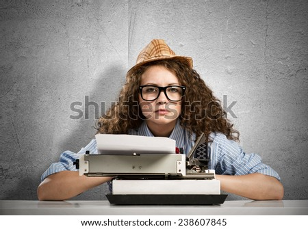 Young pretty woman writer with typing machine - stock photo