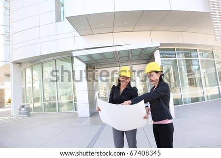 Young pretty women architects at work on building  site - stock photo