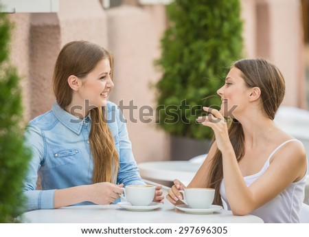 Young pretty women having great fun at urban cafe in summer and enjoying coffee. - stock photo