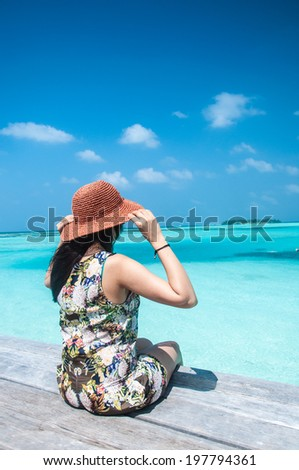 Young pretty women in floral dress enjoying the tranquil sea view - stock photo