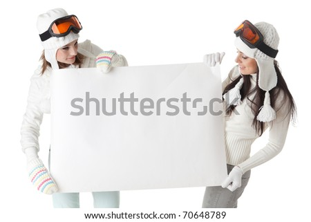Young pretty women in ski glasses and winter clothes with empty board for the text on a white background. - stock photo