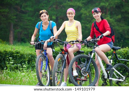 Young pretty women  race on bicycle in green park - stock photo