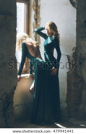 young pretty women with long lush curly blonde hair and thoughtful face in green dress standing near stony wall and big window sunny day