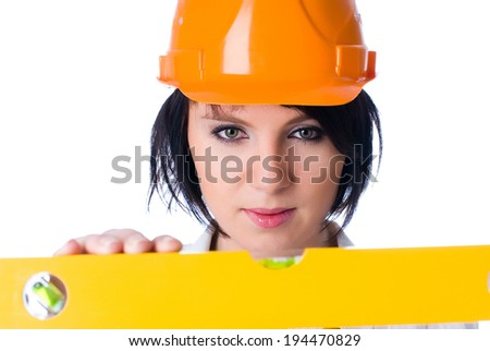 Young pretty worker with protection helmet and level at isolated background