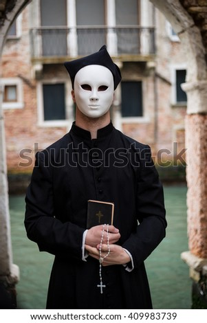 young priest in venice wearing mask  in front of canal - stock photo