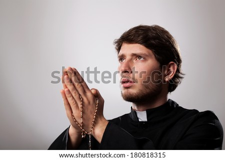 Young priest is earnestly praying the rosary - stock photo