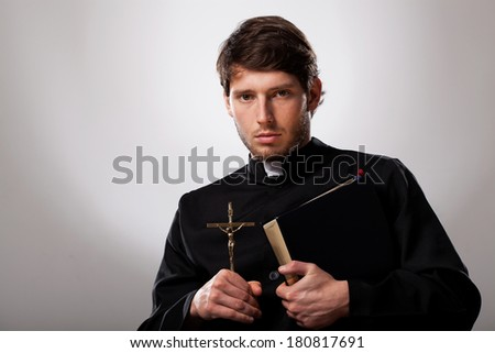 Young priest is holding a cross and holy bible - stock photo