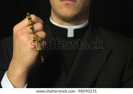 Young Priest praying with Rosary in hand