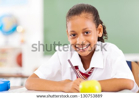 young primary schoolgirl sitting in classroom - stock photo