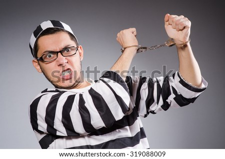 Young prisoner in handcuffs against gray - stock photo