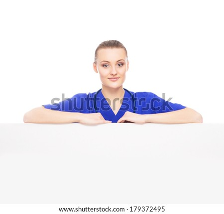 Young, professional and cheerful female doctor standing over big blank billboard isolated on white - stock photo