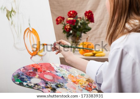 Young professional artist painting nature on canvas - stock photo