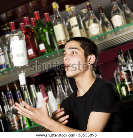 Young professional barman in action