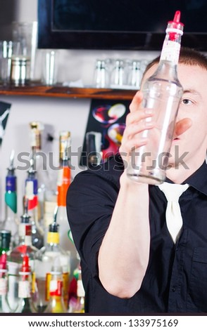 Young professional barman in action with  bottle making cocktail drinks - stock photo
