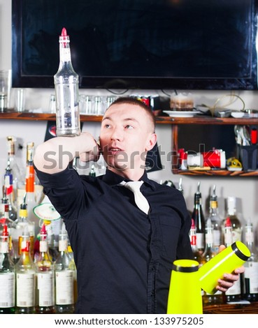 Young professional barman in action with shaker making cocktail drinks - stock photo