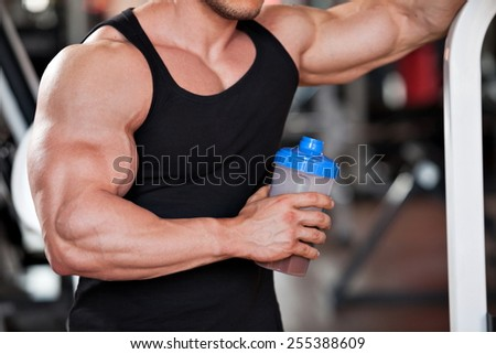 young professional bodybuilder in the gym, drinking a protein shake - stock photo