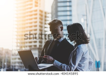 Young professional businessman and businesswoman working on a new project of building construction,  business people working on project of modern living house and discussing graphics on laptop - stock photo