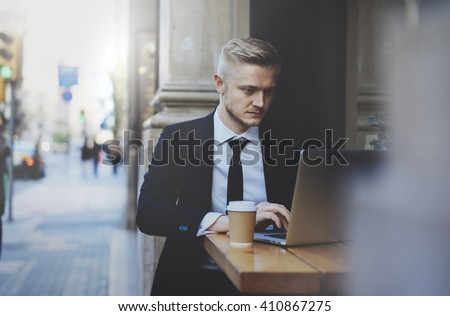 Young professional businessman wearing suit and using modern laptop outdoors, successful manager working in cafe during break and searching information in internet on his portable computer - stock photo