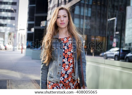 Young professional Caucasian woman walking on city street on a bright sunny day