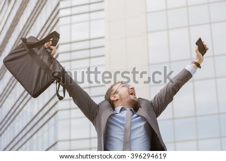 Young professional celebrating his success with hands up     - stock photo