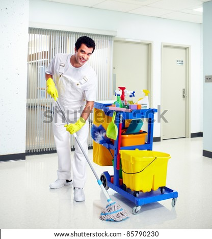 Young professional cleaner washing the floor. Janitor cart. - stock photo