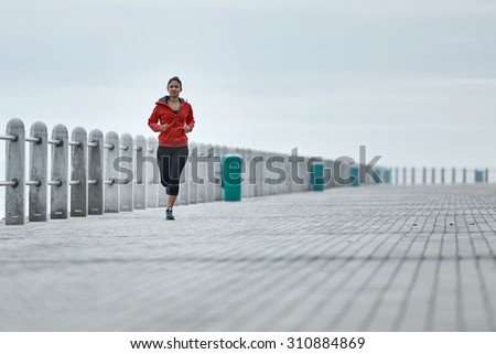 Young professional female athlete busy jogging along the ocean side on the promenade early in the morning - stock photo