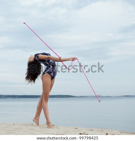 young professional gymnast woman dance with skipping rope - outdoor sand beach