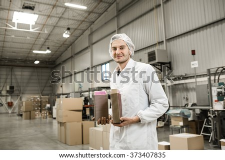 Young professional in warehouse for food packaging. Manager is standing a holding the plastic boxes for paste in automated production line for food packaging in modern factory.  Color toned image. - stock photo