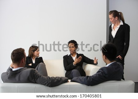 Young professional interracial business team wearing formal clothes relaxing in the break sitting on sofas and talking