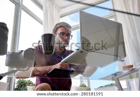 Young professional male photographer working in his home studio shot from below through his glass desk as he edits his images on his laptop computer - stock photo