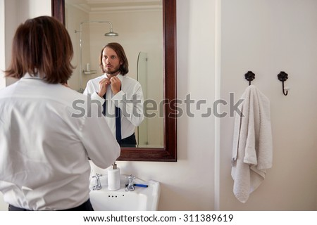 young professional man doing morning routine shirt and tie in bathroom mirror - stock photo