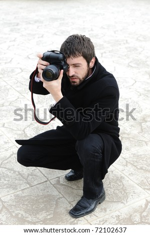 Young professional man with camera shooting outdoor - stock photo