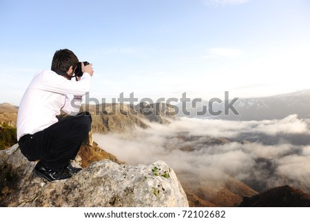 Young professional man with camera shooting outdoor, fantastic landscape - stock photo