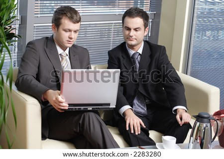 young professional men sitting at the leather sofa and working at laptop