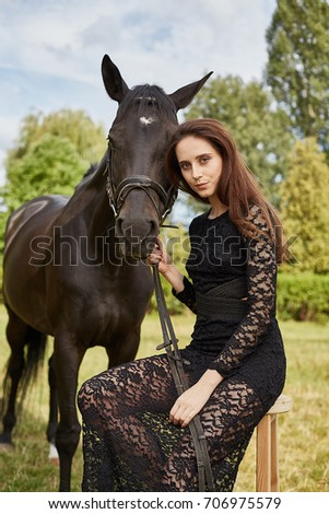 Young professional model girl posing and being photographed with horses and with a horse in different clothes.