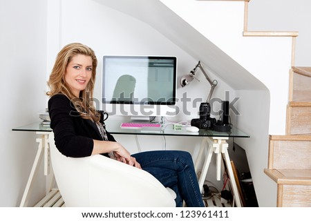 Young professional photographer working from home and sitting at her desk at home, with her camera equipment. - stock photo