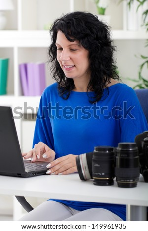 Young professional photographer working from home  with her camera equipment.  - stock photo