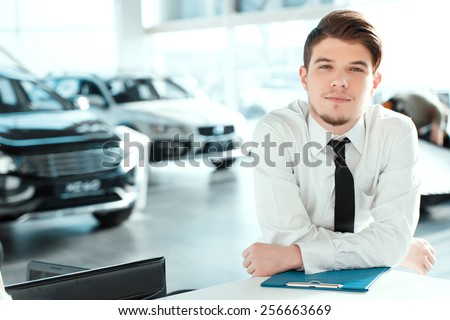 Young professional.  Portrait of handsome young sales man in formalwear posing with a note pad in car dealership  - stock photo