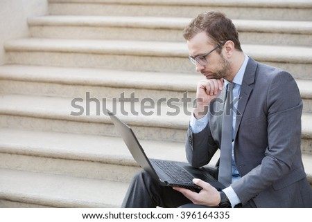 Young professional sitting on the steps with the laptop on his knees outdoors. Businessman is looking at laptop screen and thinking about the next strategic moves. - stock photo