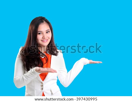 Young professional woman giving presentation with her hands showing copyspace on blue background - stock photo