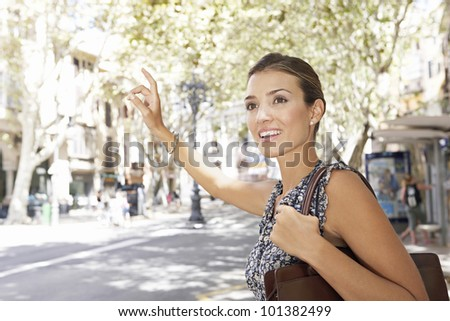 Young professional woman hitching a taxi in the financial district, smiling. - stock photo
