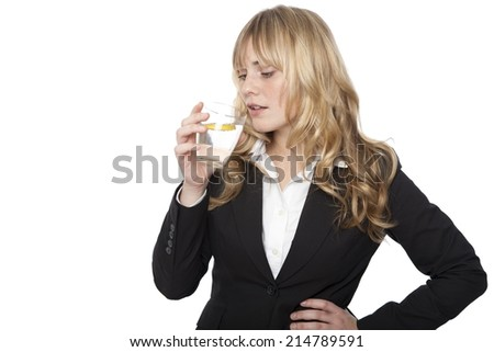 Young professional woman in a smart black jacket standing quenching her thirst drinking a glass of healthy pure water and lemon, on white