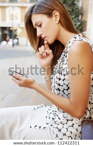 Young professional woman using a smart phone in a classic city, being thoughtful. - stock photo